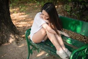traurige einsame Frau, die allein auf einer Bank im Park sitzt foto
