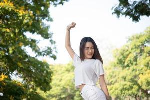 Porträt eines Mädchens, das Arme hebt und im Park lacht foto