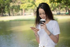 junge Frau, die Kaffeetasse hält, während Smartphone draußen verwendet