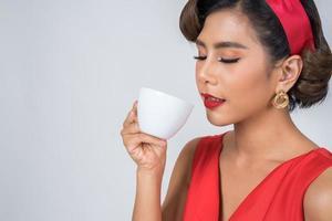 glückliche modische Frau, die eine Kaffeetasse hält foto