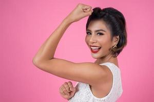 glückliche modische Frau, die ihre Muskeln zeigt foto