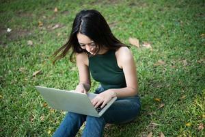 junge schöne Frau, die auf grünem Gras sitzt und Laptop im Park benutzt foto