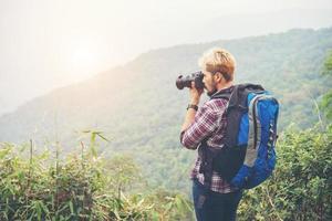 Rückseite des jungen Reisenden mit Rucksack, der auf Berg steht und ein Foto macht