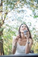 junge Frau, die wegwerfbare Kaffeetasse hält, während draußen sitzt