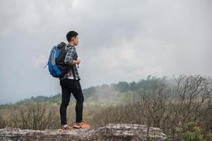 junger Hipster-Wanderer mit Rucksack, der oben auf dem Berg sitzt foto