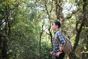 junger Hipster-Mann Wanderer, der sich beim Wandern ausruht foto