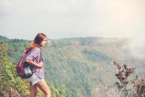 Wanderer mit Rucksack, der oben auf einem Berg steht und Naturblick genießt foto