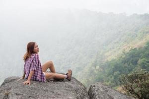 junger Wanderer mit Rucksack sitzt am Rande der Klippe foto