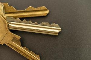 goldfarbene Türschlüssel auf einem grauen Tisch foto