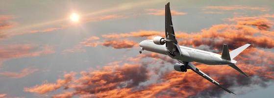 Verkehrsflugzeug im Flug gegen bunten Himmel foto