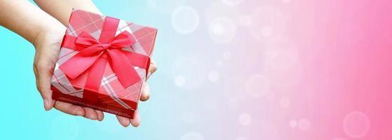 Hände halten eingewickelte Geschenkbox gegen bunten Hintergrund