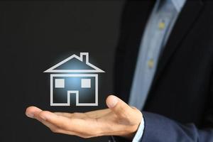 Konzeptbild des Geschäftsmannes und Symbol der Haus- oder Sachversicherung