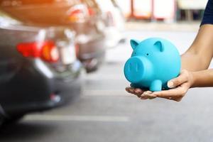 Hände halten blaues Sparschwein mit unscharfen Autos im Hintergrund