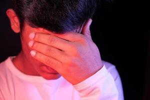Nahaufnahme des traurigen Mannes, der Gesicht mit Hand bedeckt foto