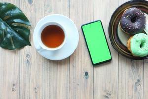 Draufsicht des Smartphones mit leerem Bildschirm, Tee und Donuts auf Tisch foto