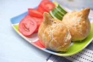 Singara Curry Puff mit Salat auf Teller