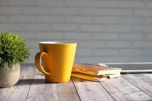Notizblock, digitales Tablet und gelbe Kaffeetasse auf dem Tisch in der Sonne foto