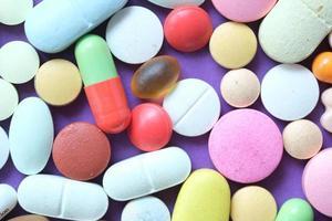 Nahaufnahme vieler bunter Pillen und Kapseln auf farbigem Hintergrund