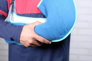 junger Mann, der eine Armstütze für gebrochene Hand trägt foto