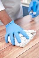 Person Hand in Einweghandschuhen mit Desinfektionsspray zur Reinigung der Tischoberfläche