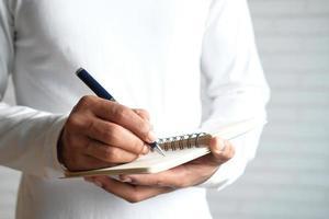 Nahaufnahme eines Mannes in einem lässigen weißen Hemd, das auf Notizblock schreibt foto