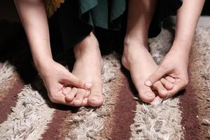 junge Frau massiert auf Füßen und leidet unter Schmerzen