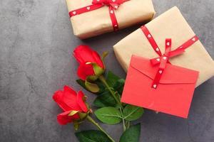 Draufsicht des Valentinstagsumschlags und der Rosenblume auf schwarzem Hintergrund