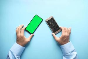 Nahaufnahme der Hand des Mannes, die das kaputte Display des Smartphones hält