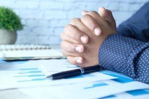 nachdenkliche Männerhand mit Stift auf Papier auf Schreibtisch