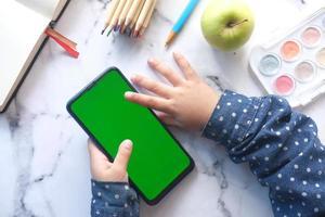 flache Zusammensetzung des Kindes mit Smartphone auf dem Tisch foto