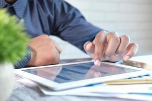 junger Mann, der Finanzdiagramm auf digitalem Tablett analysiert