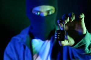 Internet-Sicherheitskonzept mit Mannhand, die Vorhängeschloss im Dunkeln hält foto