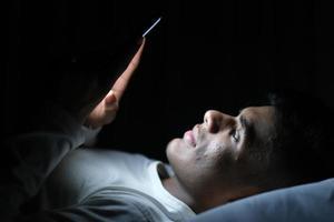 junger Mann auf dem Bett, der Smartphone nachts betrachtet