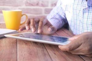 Geschäftsmann, der Finger auf digitalem Tablettbildschirm auf Schreibtisch zeigt