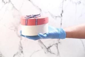 männliche Hand in einem blauen medizinischen Handschuh gibt ein Geschenk