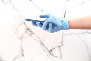 Arzthand in Schutzhandschuhen mit einem Smartphone foto