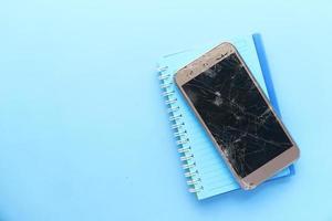 Draufsicht des gebrochenen Smartphones auf Farbhintergrund