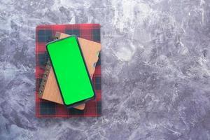 Draufsicht auf Smartphone und Notizblock auf dem Tisch foto