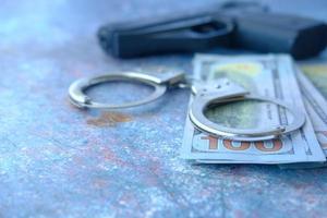 Nahaufnahme von Handschellen, Bargeld und Pistole auf neutralem Hintergrund foto