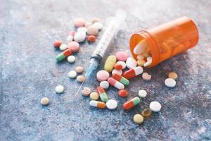 Spritze und Pillen auf dunklem Hintergrund, Nahaufnahme foto