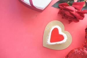 Draufsicht des Herzformkuchens, der Geschenkbox und der Rosenblume auf rotem Hintergrund
