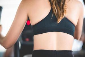 Ansicht des Frauenrückens, der schwarze Sportbekleidung auf Fitnessgeräten trägt