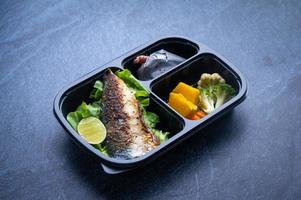 geschnittener Plastiknahrungsmittelbehälter mit Salat, gegrilltem Fisch und Gemüse