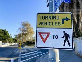 Ein sich drehendes Fahrzeug gibt dem Fußgängerzeichen nach foto