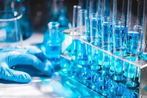 Hand in blauem Handschuh mit Fläschchen mit blauer Flüssigkeit foto