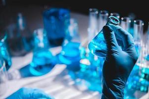 Hand in blauem Handschuh, der Kolben der blauen Flüssigkeit mit Flaschen und Fläschchen der blauen Flüssigkeit im Hintergrund hält foto