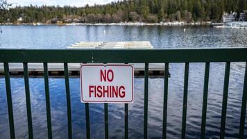 An einem sonnigen Tag ein Schild ohne Fischfang am Pier foto