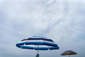 zwei Sonnenschirme auf einem wolkigen blauen Himmel