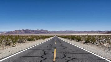 Wüstenstraße mit ausgebessertem Asphalt foto
