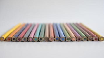 benutzte Buntstifte auf einem weißen Tisch, wobei die unteren Teile der Kamera auf einem verschwommenen Hintergrund zugewandt waren